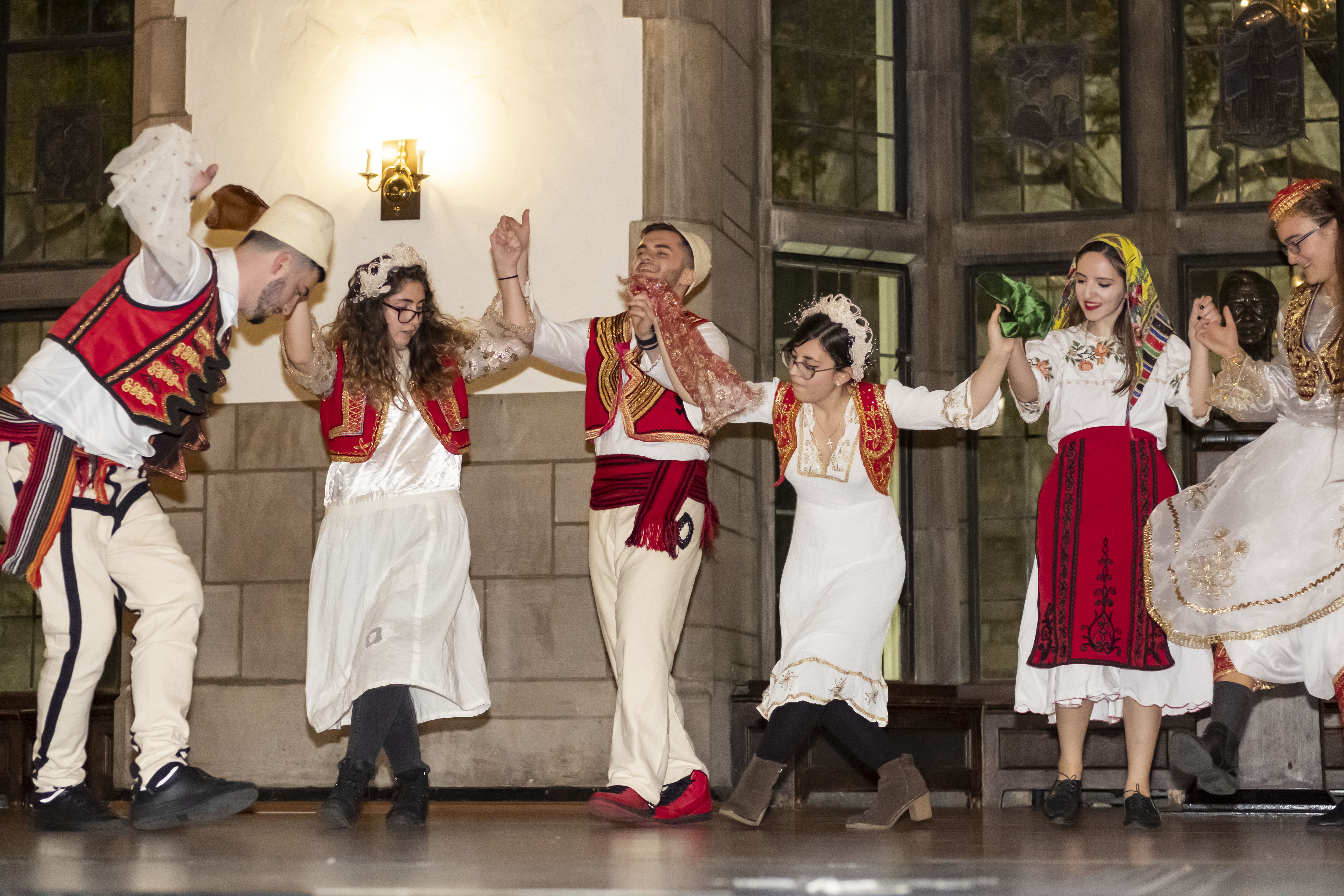 Albanian students performing dance on stage.