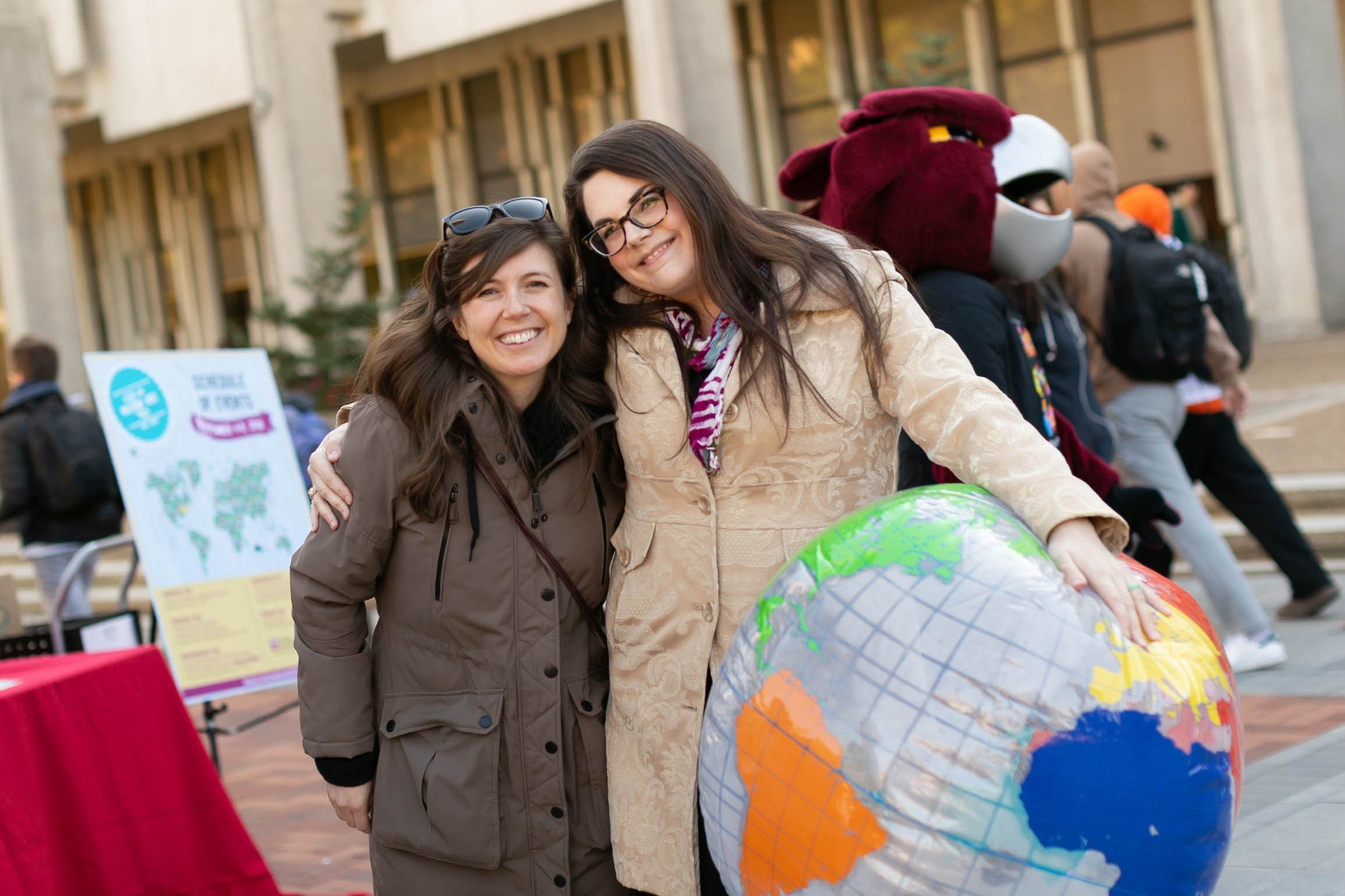 Two smiling women holding a blow-up globe.