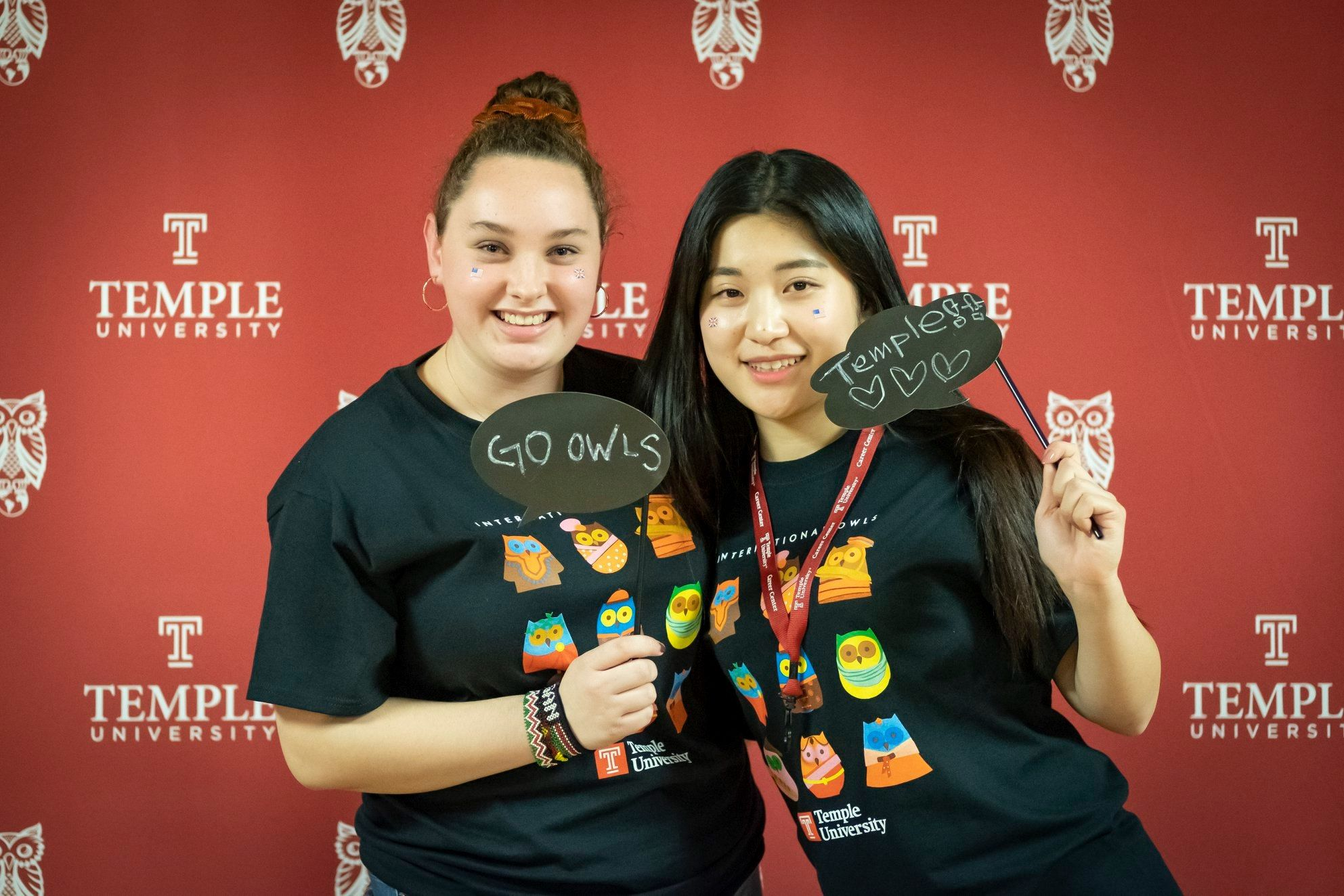 Two students posing at the selfie wall