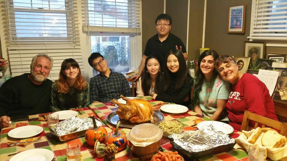 Family and students posing at the dinner table